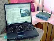 一台黑色笔记本电脑与一台放在后面的无线路由器