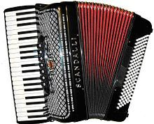 A picture of a red and black button accordion
