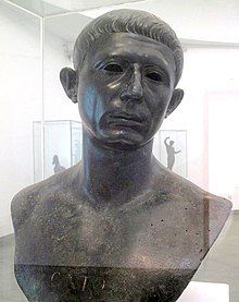 """A bronze bust of the head and shoulders of a middle-aged man, with the word """"CATO"""" inscribed across the chest"""