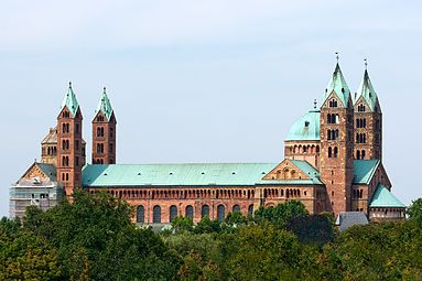An enormous cathedral, of red stone with green copper roofs, has a two tall towers framing an octagonal dome at each end of the building.