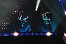 Two robotic figures can be seen looking down. Strips of LED lights and spotlights surround them.