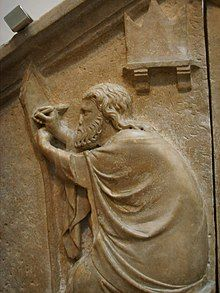A relief against a wall shows a bearded man reaching up with his hands as his clothes are draped over his body.