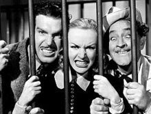 Fred MacMurray, Carole Lombard and Barrymore making funny faces behind prison bars; MacMurray and Lombard fiercely show their teeth, while Barrymore crosses his eyes goofily