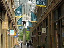 """Atrium of a shopping arcade, with green and yellow banners hanging overhead with the words """"Nickels Arcade"""""""