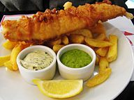 A large piece of battered fish on a plate of chips, served with ramekins of tartar sauce and mushy peas