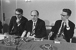 Andreas Papandrou flanked by two men seated at a table in front of microphones