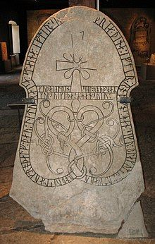 A rounded stone with an inscripted cross and runes