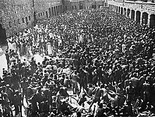 A group several hundred naked men is crowded in an enclosed courtyard, with garage doors visible on three sides.