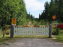 A simple white fence with a red and yellow gate behind it set across a dirt path in a green forest.