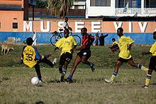 five men playing football one red and black striped jersey and four in yellow jersey
