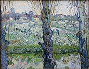 A close view of three blossoming trees behind which can be seen a large orchard and field in which a man is working, a village filled with buildings and houses in the background, under a bright sky