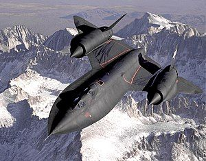 Dryden's SR-71B Blackbird, NASA 831, slices across the snow-covered southern Sierra Nevada Mountains of California after being refueled by a USAF tanker during a 1994 flight. SR-71B was the trainer version of the SR-71. The dual cockpit allows the instructor to fly.