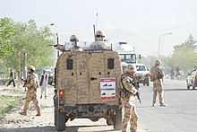 Armed soldiers in and around a military vehicle