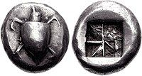 Both sides of a silver coin. One side has a relief of a turtle; the other the impression of a square divided into eight segments.
