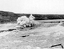 View of an explosion atop a dam in a flooding river