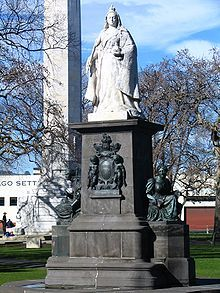 Large figure of a woman wearing a crown and robes, positioned on a tall plinth
