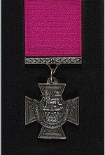 """A bronze cross pattée bearing the crown of Saint Edward surmounted by a lion with the inscription """"for valour"""". A crimson ribbon is attached"""