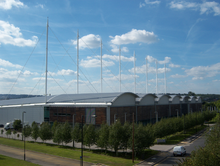 A Modern sporting facility. The building is roughly rectangular in shape and is quite modern, with a wooden clad design. It is surrounded by greenery and has several tall, white spikes on its roof.