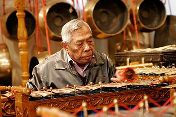 Man playing a gamelan, a traditional Indonesian instrument