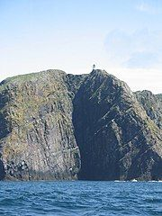 A small white building is barely visible on top of dark and imposing cliffs with deep blue water at their base.