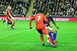 Luis Suárez in Liverpool kit clashes with Sylvian Distin in Everton kit.