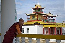 Buddhist monk in Siberia in robes leaning on railing looking at temple