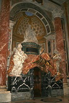 A large memorial set in a niche. The marble figure of a kneeling pope is surrounded by allegoric marble figures, and sculptured drapery surfaced with patterned red stone.