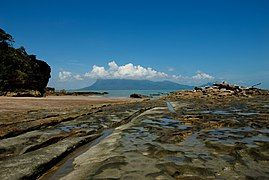 A mudflat receding into the sea in the distance, with a cloud-topped mountain beyond