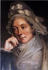 Quarter-length portrait of a woman in a brown and grey lace bonnet adorned with a bow and leaning on her right hand.