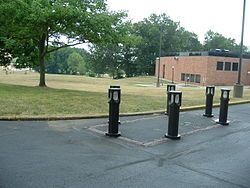 Color photograph of memorial (six posts with lights set around a rectangular demarcation) with grass, trees, and a building in the background.