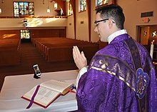 A man wearing purple vestments and standing at an altar uses a mobile phone camera to record himself. Empty pews are visible in the background.