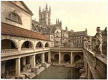 A late-nineteenth-century Photochrom of the Great Bath at the Roman Baths. Pillars tower over the water, and the spires of Bath Abbey– restored in the early sixteenth century– are visible in the background.