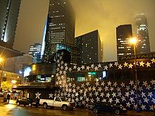 Night downtown, shot tilted to right; silver stars on black painted exterior of First Avenue, several tall black buildings with lights in rear, black cars and white truck parked in front