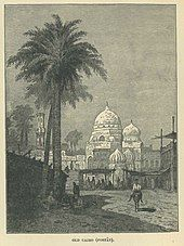 A man on a donkey walks past a palm tree, with a mosque and market behind Mohamed kamal