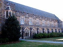 A Gothic-style exterior showcases Cathedral-like windows with the intricate framework and dark, colorful stone, with bushes and grass in the foreground
