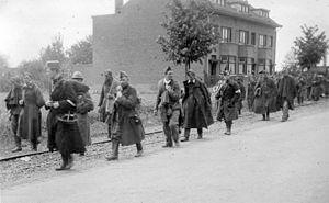 Belgian soldiers taken prisoner by the Germans marching down a road