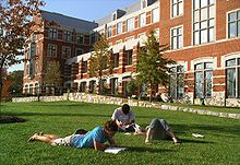 Three young adults lie on grass reading books in front of a brick building with many windows.