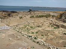 The remains of the wall of a small structure are seen in the foreground, the Sea of Azov is visible in the background.