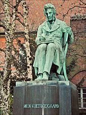 """A statue. The figure is depicted as sitting and writing, with a book on his lap open. Trees and red tiled roof is in background. The statue itself is mostly green, with streaks of grey showing wear and tear. The statue's base is grey and reads """"SØREN KIERKEGAARD"""""""