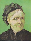 A closeup portrait of an elderly well-dressed woman sits facing to her left (the viewer's right). She has a pleasant smile and she is dressed in a dark top and she is wearing a hat, in front of a vivid green background.