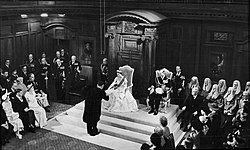 Queen Elizabeth II opening a session of the New Zealand Parliament on 12 January 1954 in the Legislative Council Chamber, Parliament House. She is accepting a vellum copy of her speech from the throne from Sir Sidney Holland (Prime Minister, 1949-1957).