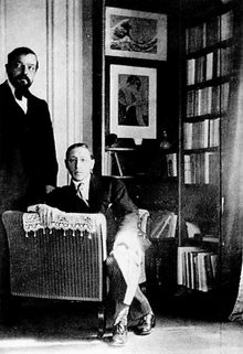 two white men, one bearded, middle-aged, standing, one younger, seated, in a book-lined room