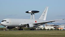 Side view of Japan military reconnaissance aircraft on airport runway, with dorsal mounted sensor pallet