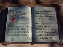 """A sculpture in the form of an open book. The text of the poem """"In Flanders Fields"""" is written within and a small red poppy lies on top."""