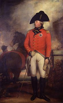 George wearing the red jacket of an 1800 British army general with the star of the Order of the Garter, white breeches, black knee-high boots, and a black bicorne hat. Behind him a groom holds a horse.
