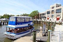 Modern color photo of a boat on a sunny day docked to a wharf with a large building behind it