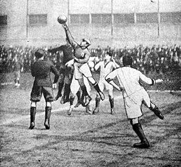 Old cartoon of an association football match with the goalkeeper in the middle who jumps and hits the ball