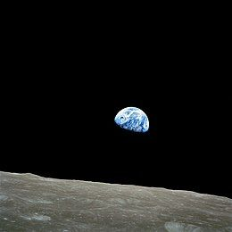 A black sky with a grey, cratered lunar horizon. A small blue Earth with scattered white clouds is just above the horizon,with about two-thirds of the Earth lit by the Sun and the remainder in darkness.
