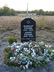 A Memorial for Margot and Anne Frank shows a Star of David and the full names, birthdates, and year of death of each of the sisters, in white lettering on a large black stone. The stone sits alone in a grassy field, and the ground beneath the stone is covered with floral tributes and photographs of Anne Frank