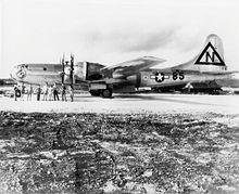 一架大型四引擎飞机停在跑道上,前面站着九名机组人员。